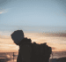Young man with backpack looks off towards sunset where sky meets horizon