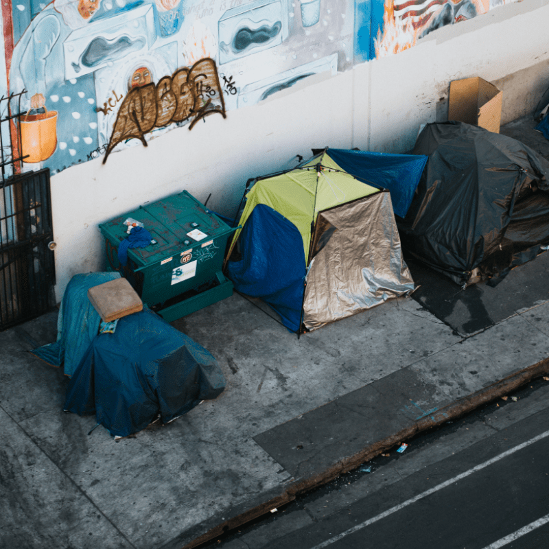 Several tents against a graffiti wall alongside an urban street
